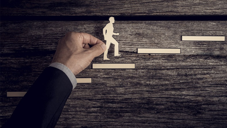 Retro style image of a successful businessman climbing the corporate ladder using paper cutouts. - Image