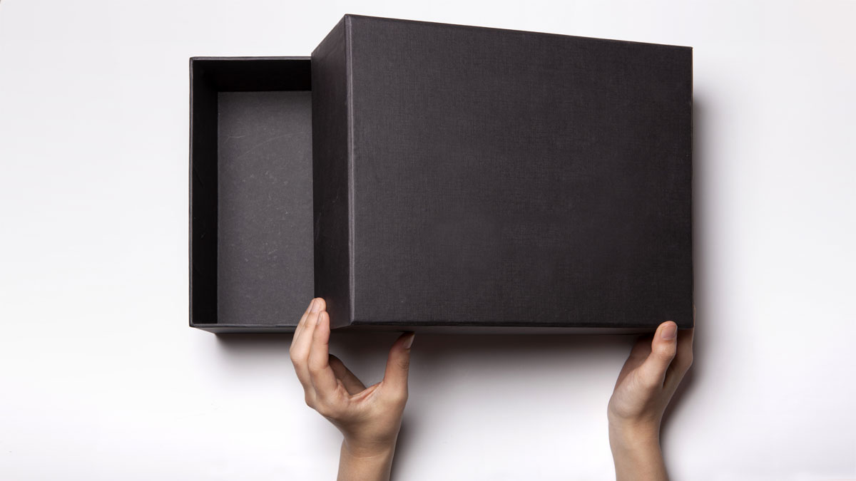 A female(woman, girl) two hands hold and open the empty(blank) black box isolated white, top view at the studio.